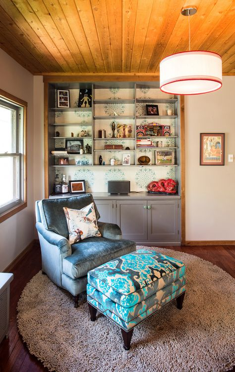 Small Seating Area,Side Chair, Damask Fabric Osbourne  Little, Contrasting Ottoman, Built-in Shelving  Cabinets with Harlequin Wall Paper on Back Wall, Drum Shade Pendant, Round Plush Rug