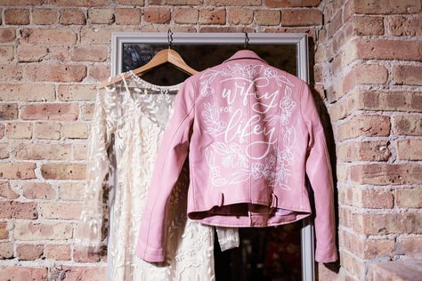 Bride's long sleeve illusion dress and custom pink leather jacket hanging at The Joinery Chicago