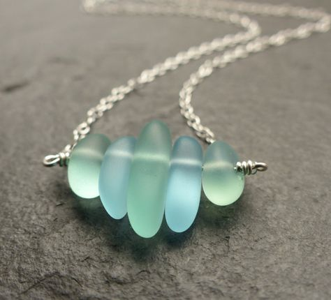 This dainty sea glass necklace is full of the sparkle of foamy waves as they crash on a sandy bay.  The cultured sea glass is made from recycled