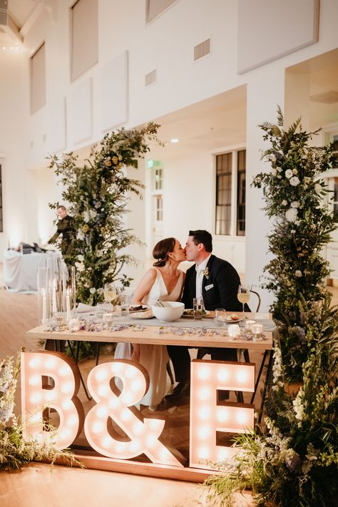 Dreamy headtable inspo for this indoor San Diego wedding at Building 177! Giant marquee lights and incredible greenery and florals. Photo by Kami Olavarria