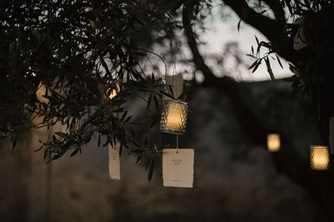 Create a romantic outdoor atmosphere by hanging love letters in the trees alongside lit candle votives at a summer evening wedding. Click through for more rustic wedding ideas! #rusticwedding #weddinglights #summerwedding #eveningwedding #romanticweddingideas