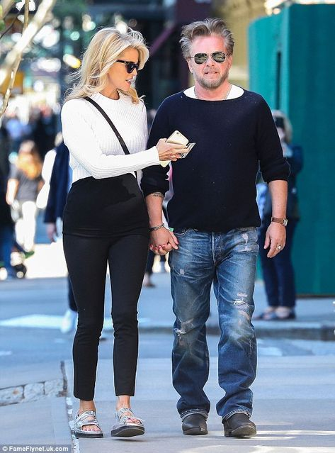 Hand in hand: He covered his eyes with a pair of aviators and sported rugged stubble while...