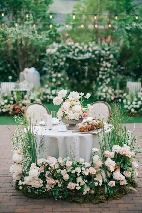 A beautifully decorated Head Table for a Mini Wedding. The floral arrangements are outstanding! #headtable #wedding #miniwedding #weddingdecor #flowers #floralarrangements #tablescape #outdoorwedding #perfectaffair Weddingdesign #weddingideas #weddingstyle