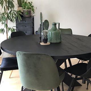 Zwarte kast en houten tafel met industriële stoelen