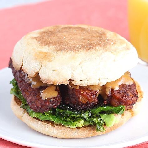A vegan breakfast sandwich loaded with all the goods: creamy avocado, almond butter, sautéed kale and tempeh bacon, served on a perfectly toasted english muffin.   #breakfastsandwich #veganbreakfastsandwich #tempehbacon #eatingbirdfood