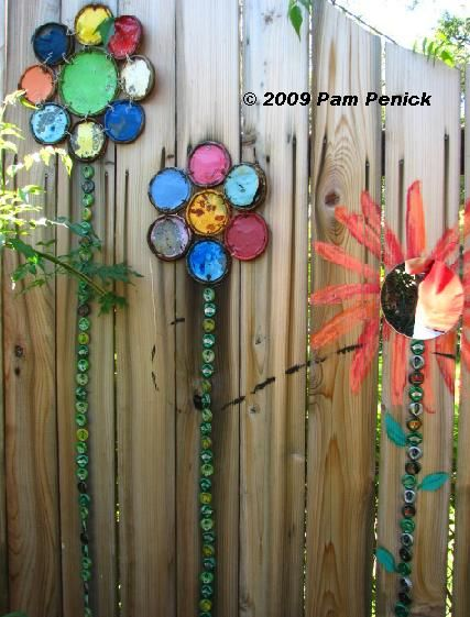 Paint can lids and circular mirrors with bottle caps make this fence-side garden adorably colorful.