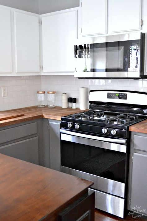 White upper cabinets | gray lower cabinets | butcher block counters | stainless steel appliances | copper accents | #kitchenmakeover #butcherblock #kitchenideas #whitecabinets #graycabinets