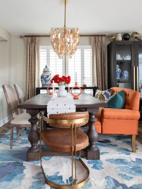 A orange settee, a capiz pendant and a blue patterned rug give make this eclectic dining room pop. See more on HGTV.com.