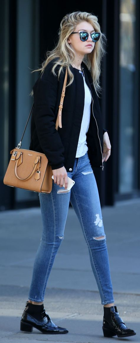 GiGi Hadid in a black bomber jacket and black ankle boots with Michael Kors Casey Small Satchel Bag. See how you can get this look for less!