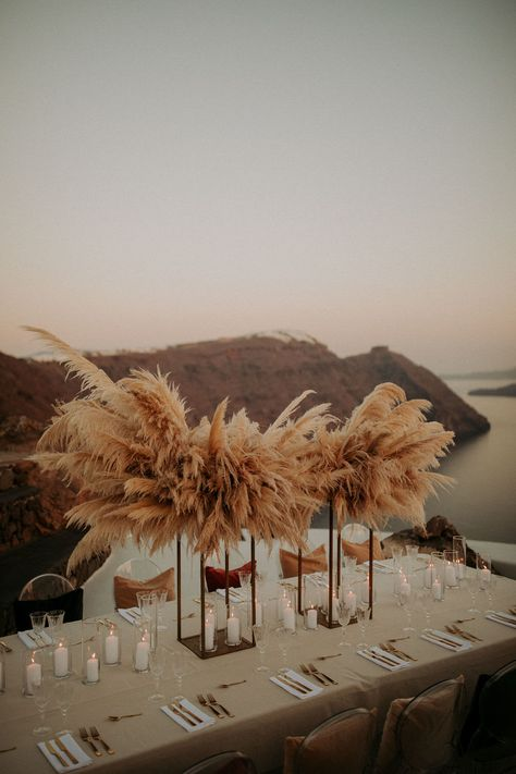 We have officially found the destination wedding of our dreams in Santorini, Greece! From the dried botanical  pampas grass wedding arch to the pop of colorful pillows in the ghost chair during the reception, we love it ALL!