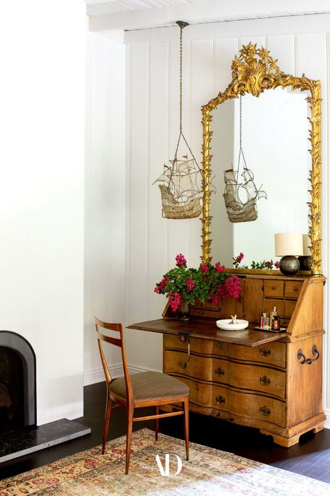 In the main bedroom, a Regency gilt-wood mirror surmounts an 18th-century Danish secretary. A Baguès ship-form chandelier hangs from the ceiling, and the side chair is by Ico Parisi. All the elements come together to create a sophisticated, yet eclectic corner reflecting the rest of the home which is filled with more eccentric heirlooms and curiosities. #bedroom #fireplace #vanity #mirror #dresser #chair #rug #woodpanels #shiplap #antiques #cozy #ranchhome #ranchhouse #eclectic #ornate #desk