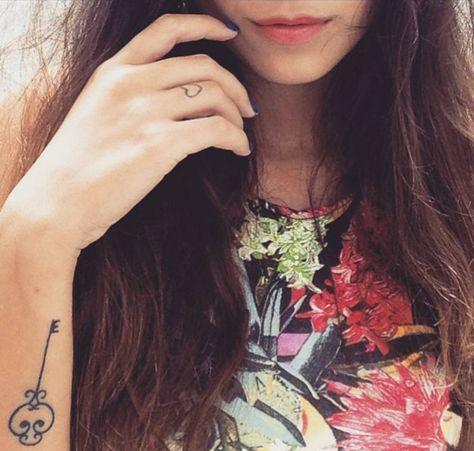 Tatuaje de una llave en el antebrazo de Mariana, y otro pequeño tatuaje de un corazón en su dedo anular derecho.