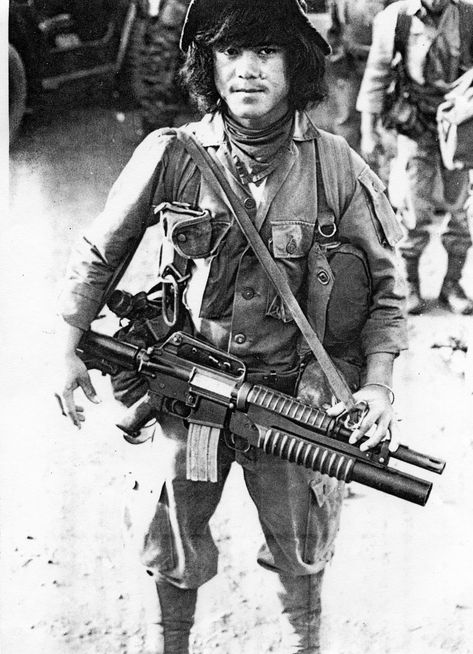 Indig team member with an XM-177E2 with attached XM-148 40mm grenade launcher. Gas mask carrier under left arm. Could be used to carry other gear too.
