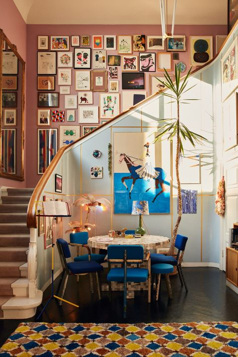Blue and pink living space with large gallery wall in the staircase in a colorful art-filled home