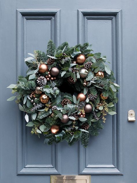 A sumptuous array of seasonal foliage, beautiful copper and mink baubles, frosted pine cones and miniature copper bells. The perfect centrepiece for your front door.
