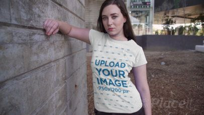 Placeit - T-Shirt Video Featuring a Serious-Looking Woman by a Concrete Wall