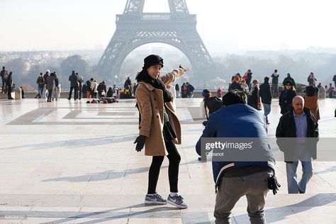 A tourist poses in front of the Eiffel Tower surrounded by