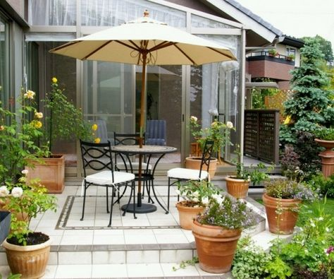 small patio courtyard clay pots flowers wrought iron furniture set parasol