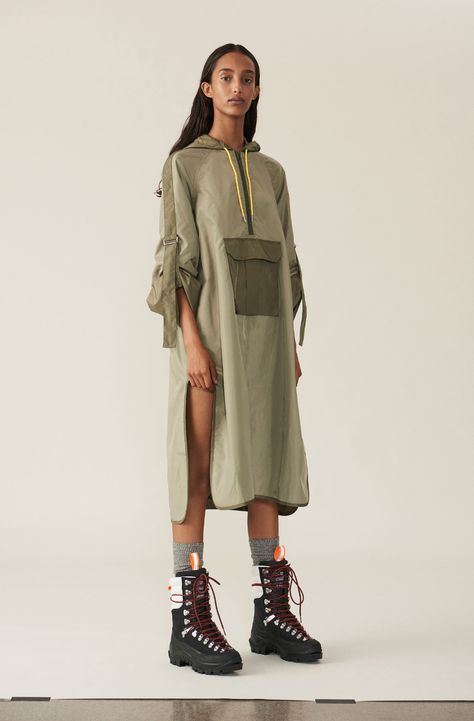 Oversized jacket with front pocket, zip closure and a hood with yellow drawstrings. The sleeves are wide and adjustable in length with tie straps and metal clasps. The jacket is inspired by camping and the great outdoors.Final Sale