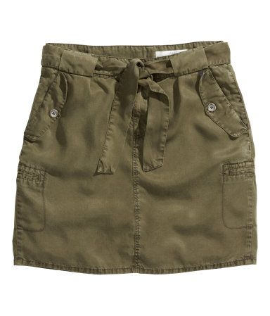 Knee-length cargo skirt in Tencel® lyocell with a tie belt at the waist, pockets with a decorative flap at the front, side pockets, and fake pockets…