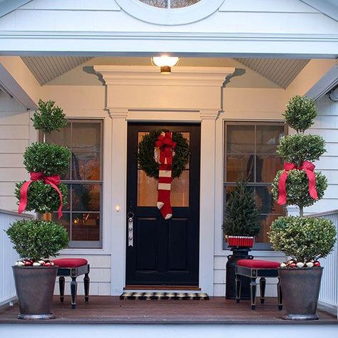 Unsure of design choices when it comes to outdoor holiday decorating? Pick the easiest principle to implement: symmetry. Here, matching topiaries and benches offer soothing visuals, while an oversize stocking dresses up the front-door wreath. http://www.bhg.com/christmas/outdoor-decorations/holiday-inspired-outdoor-decorating-that-lasts/?socsrc=bhgpin121914symmetricaldoordecor&page=27