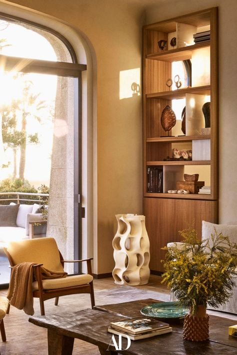 When they were ready to downsize from their nearby villa, a couple turned to their architect son to combine three stellar apartments into their dream home. The lounge is furnished with two coffee tables and armchairs making it a warm and cozy space to relax. #livingrooms #livingroomideas #livingroominspo #design #wood #ceramic #minimalist #brutalist #armchairs #coffeetables #bookshelf #vase #floorlamp #sofa #couch