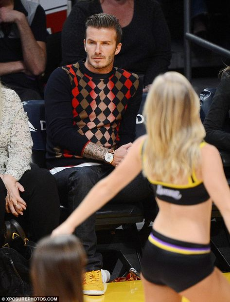 Look away! David Beckham tries very hard not to look at the scantily clad Lakers girl, despite her best efforts