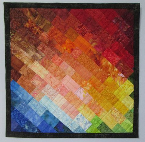 Size: 18 x 18; this is a colorful mosaic art quilt that reminds you of a rainbow with a whole range of colors. About 150 small fabric mosaic pieces are pieced and sewn together with colors blending one into the other for a beautiful composition. No fabric is used twice!! The wall quilt is stitched using a free motion random block design. A sleeve is attached to the upper back with a dowel and two nails included with your purchase for easy hanging.