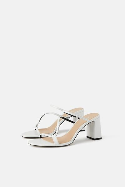 Heeled mules with asymmetrical straps