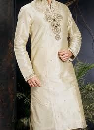 Attain a classy charm clad in this cream shade art dupion silk kurta pyjama. Kurta is enhanced with beautiful decorative buttis. Ethnic paisley and decorative patterns adorned with moti, stones, zardosi and crystals beautifies the neck patch and collar. Paired with a matching bottom.