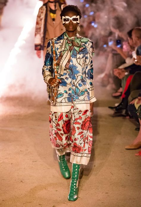 Alessandro Michele took this Gucci collection to macabre levels in the city of the dead   White and blue silk floral top over white and red pleat cropped pants with green lace-up boots. Look at those oversized sunglasses!