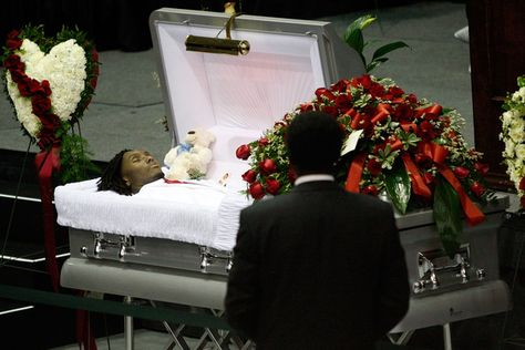 A man stands near the open casket during the funeral for Cincinati Bengals player Chris Henry at the Alario Center on December 2009 in Westwego, Louisiana.