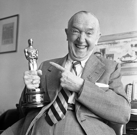 Stan Laurel holding his Academy Award Oscar presented to him for his