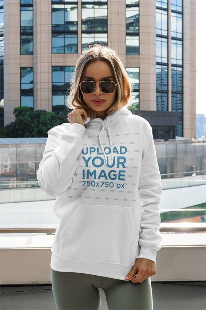 Placeit - Mockup of a Woman with a Pullover Hoodie Posing by a Tall Building