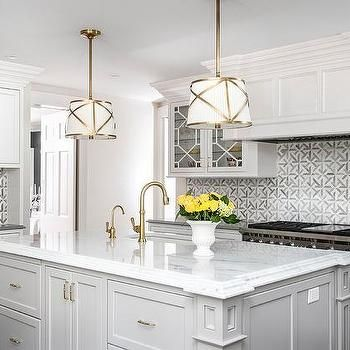 White And Gold Drum Pendant Lights Over Light Gray Island