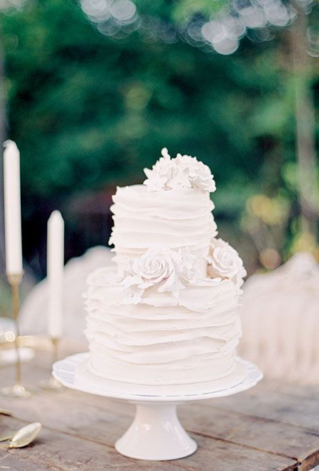 A two-tiered wedding cake with ruffles | Brides.com