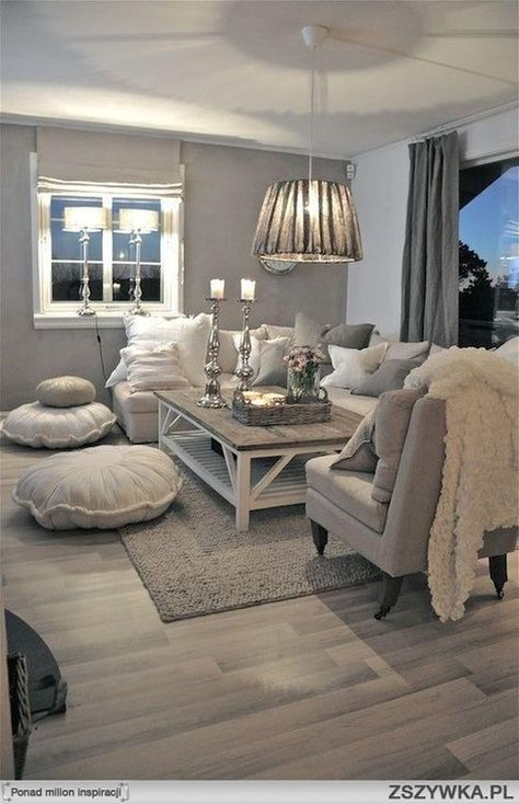 Neutral couch, grey and white pillows/ throws. Floor poufs and an accent arm chair