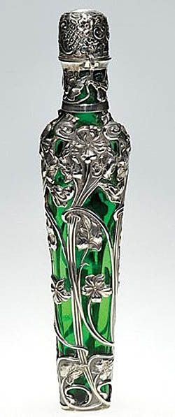 """1876 - 1925  An English silver and glass lay-down perfume bottle in green and enclosed by stemmed flowers in silver, the hinged silver cap revealing a clear stopper within. The silver is hallmarked with a rampant lion, the head of a cougar and the initials """"SJ"""" on the neck. The cap is marked with a rampant lion, an anchor, letter """"C"""" and the initials """"MJJ."""" Below the base """"Sorley Glasgo"""" is impressed."""