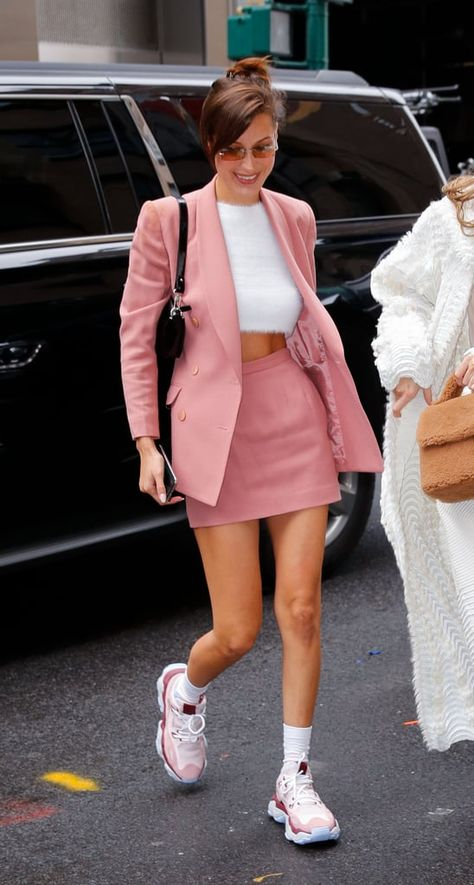 Bella Hadid a bercé un tailleur jupe rose avec un pull fuzzy Asos et des basket. Bella Hadid rocked a pink skirt suit with an Asos fuzzy sweater and Chunky Dad sneakers