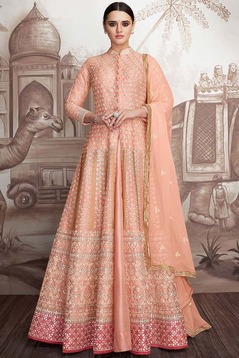 Bright and colourful, this Peach Net Anarkali Suit which will instantly catch your fancy. This Collar neck and Quarter Sleeves apparel adorned with resham, stone, dori and mirror work. Matched with Santoon/lycra Churidar in Peach Color with Peach Chiffon Dupatta This Anarkali Suit can be customised up to 58 Inches around the Bust. Slight color variation may occur due to photographic reasons.