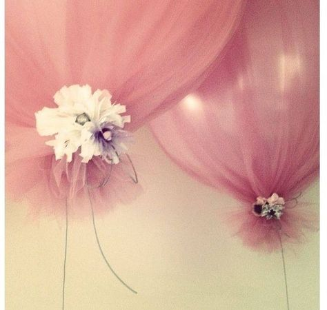 Tulle wrapped around balloons tied with flowers and ribbon