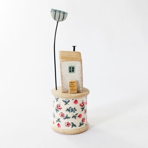 Little oak wood house and clay flower on a vintage bobbin