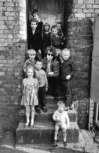 Bob Dylan hanging out in a doorway with some kids in Liverpool, England.