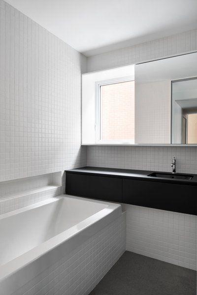 White Square Ceramic Tiles Cover The Bathroom Walls The Counters Are Fenix Laminate Arpa White Mosaic Bathroom White Bathroom Tiles Small White Bathrooms