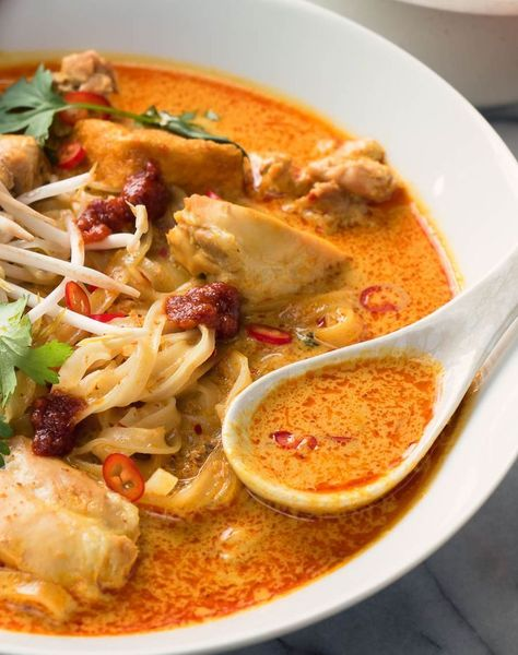 Spoon full of laksa over a bowl of coconut curry soup.