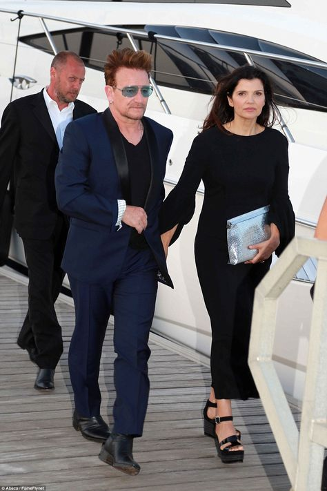 Holding on to yo(U2): His stunning wife Ali Hewson, who he has been married to for 34 years, looked slinky in a black dress with bell sleeves and a ankle-grazing hemline
