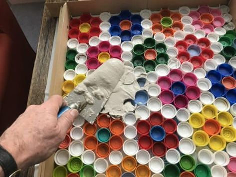 An old garden coffee table with a broken surface is given new life with a new surface made from upcycled plastic bottle caps.