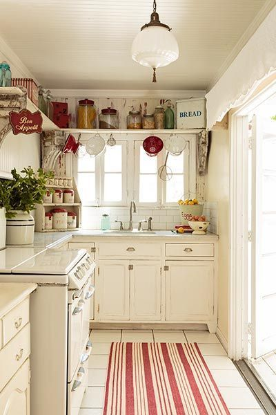 I love the red and white striped kitchen rug featured on this kitchen floor. flea market decor stands on an open shelf wrapping around the wall near the ceiling of this vintage-look kitchen in shades of white with red accents in this cottage-style remodel