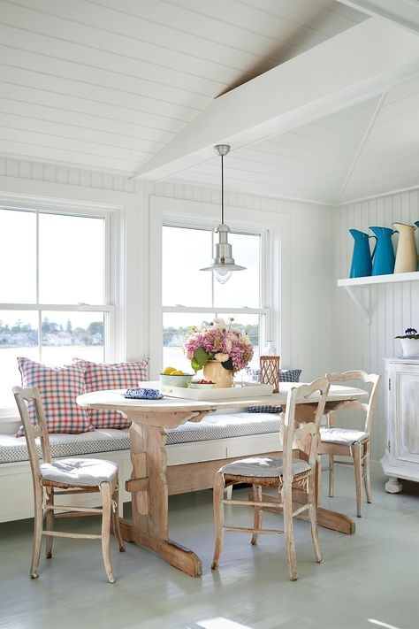In this cottage-style breakfast nook, simple wooden chairs and a table are unified with a weathered, whitewashed finish. The bench is painted in a crisp white and topped with plaid pillows that act as seatbacks without obstructing the view. #breakfastnookidea #eatinkitchen #breakfastnookbench #bhg