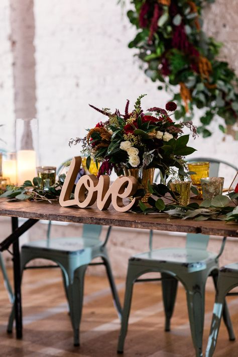 Boho and vintage head table decor with gold LOVE sign and jewel-toned florals